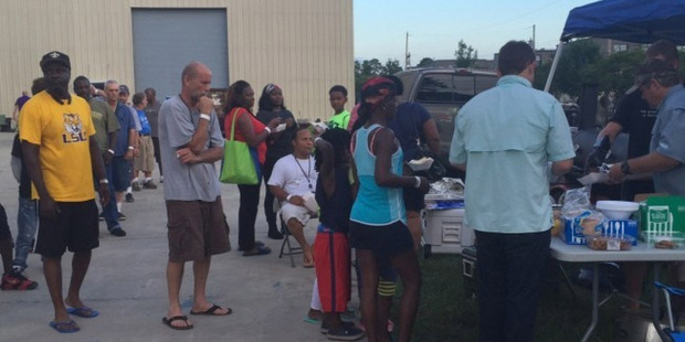 Displaced flood victims line up for a barbecue dinner. Photo / the Washington Post.