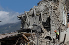 A rescuer walks a sniffer dog as they search through the debris of collapsed houses following the earthquake in Amatrice, central Italy. Photo / AP