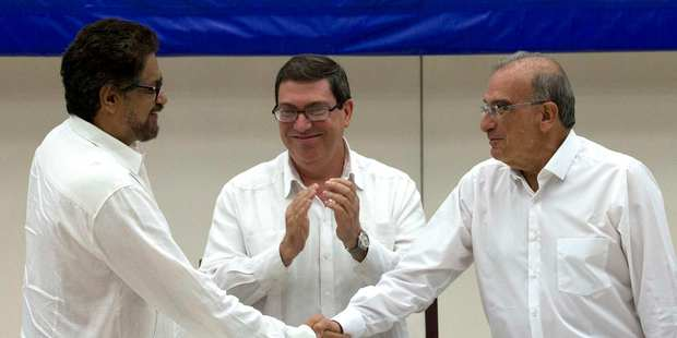 Humberto de La Calle, right, head of Colombia's negotiation team, shakes hands with Ivan Marquez, chief negotiator of Farc, left, Cuban Foreign Minister Bruno Rodriguez applauds. Photo / AP