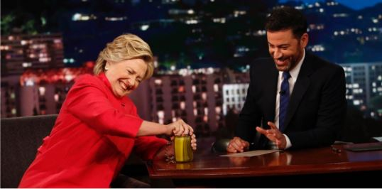 Jimmy Kimmel challenged Hillary Clinton to open a jar of pickles to prove her strength, which she did while pretending to struggle with the lid. Photo / AP