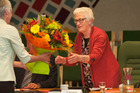 Glenys Searancke receives a bouquet of flowers from council staff at her last council meeting today.  Photo/Ben Fraser