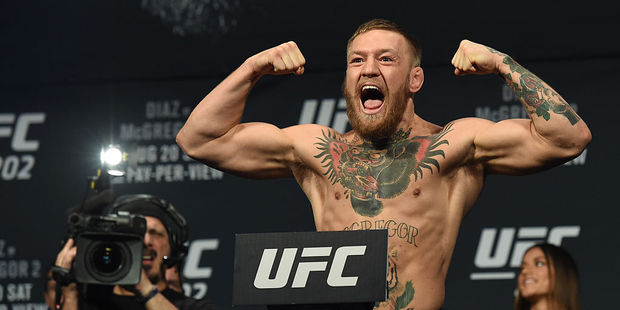 UFC featherweight champion Conor McGregor poses on the scale during his weigh-in for UFC 202. Photo / Getty Images