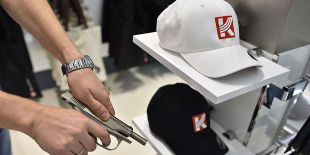 A man poses with one of the model guns on sale in the Kalashnikov shop. Photo / Getty Images