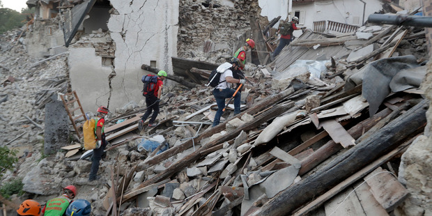 Rescuers search through debris following an earthquake in Pescara Del Tronto, Italy. Photo / AP