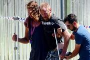 A man is walked back to the scene by fellow backpackers and a detective. Photo / News Corp Australia