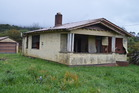 The house in Runanga without its windows. Photo / Greymouth Star
