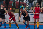 FOCUSED: Valley United's Nicki Smith, red, and Katikati's Natasha Leong, black, charge for the ball in Saturday's Midland Intercity hockey final. PHOTO/Supplied