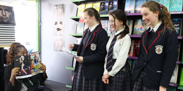 History teacher Caroline Gonouya being caught in Stratford Paper Plus by Shiyanne Jones, Shana Wilson and Diana Greensill.