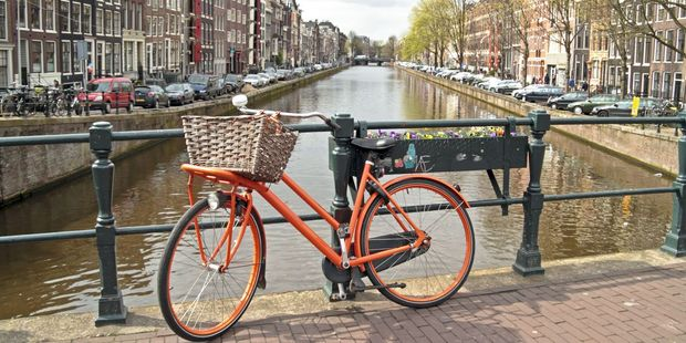 Orange bike on the bridge in Amsterdam city in the Netherlands. Photo / 123RF