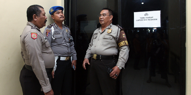 Indonesian police officers guard a door where murder suspect David Taylor is detained at police headquarters in Bali. Photo / AP