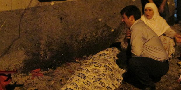 A man cries over a covered body after an explosion in Gaziantep, southeastern Turkey. Photo / AP
