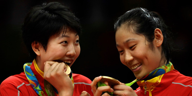 China's Yuan Xinyue, left, bites her gold medal as Zhu Ting examines hers during an awarding ceremony for women's volleyball at the 2016 Summer Olympics. Photo / AP