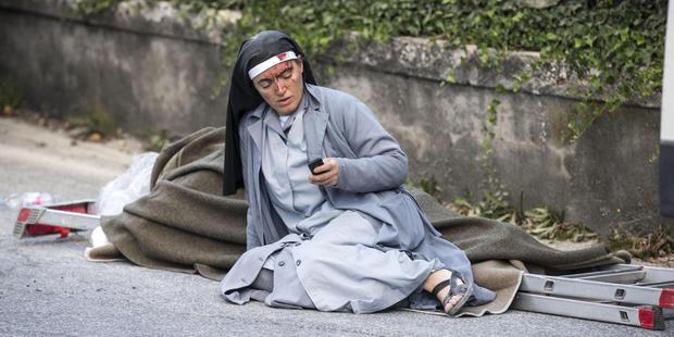 A nun checks her mobile phone as she lies near a ladder following an earthquake in Amatrice. Photo / AP