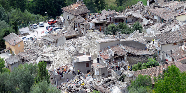 Rescuers search through debris of collapsed houses in Pescara del Tronto, Italy. Photo / AP