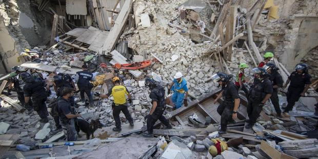 Loading Rescuers search through debris after the earthquake in Amatrice. Photo / AP