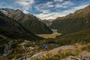 A foreign tramper has been waiting for nearly a month at a remote South Island hut to be saved after her partner was killed falling down a slope. Photo of the view looking down Routeburn Flats.