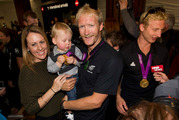Wife Jackie and son Zac welcome home gold medal winner Eric Murray and his rowing partner, Hamish Bond (right) at Auckland International Airport. Photo / Steven McNicholl