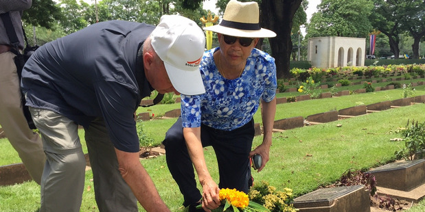 Thai Ambassador Maris Sangiampongsa and New Zealand travel photographer Paul Rush lay a poppy and wreath at the grave of a Kiwi soldier at Kanchanaburi Cemetery. Photo / Lincoln Tan