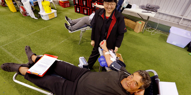 Winnie Wang watches  as Charles Frische donates blood for the 58th time in Whangarei in June. The Blood Service wants more Northlanders to donate and will be in the region over the next two months collecting blood. Photo / John Stone