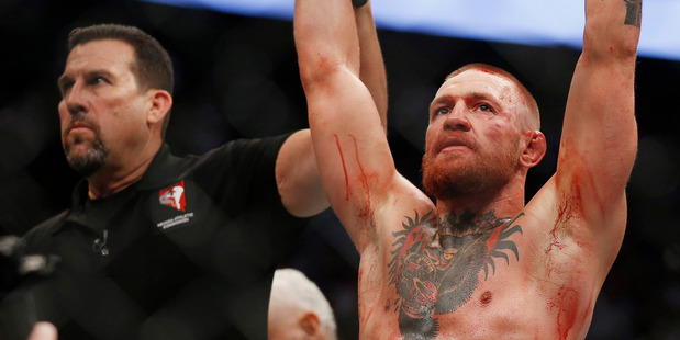 Conor McGregor (left) reacts as he is announced the winner following his welterweight mixed martial arts bout against Nate Diaz at UFC 202 on Saturday. Photo / Getty Images