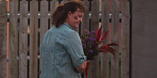 A lady arrives with flowers outside the scene where three people were stabbed. Photo / Zak Simmonds, News Corp Australia