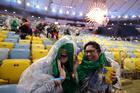 Spectators sit in the rain at the closing ceremony inside Maracana stadium in Rio de Janeiro. Photo / AP