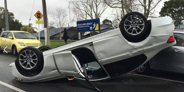 The driver of this car was treated by St John for minor injuries after it overturned outside Bucklands Beach Intermediate in Auckland this morning. Photo/Facebook
