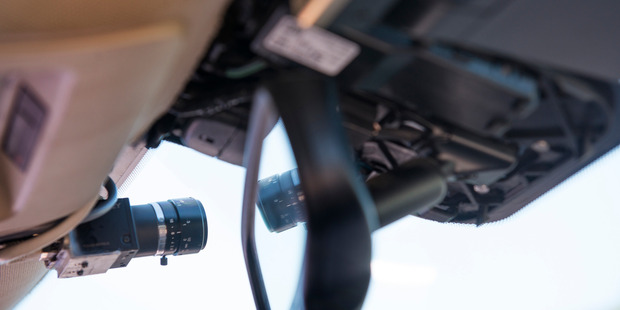 A view of a small camera mounted next to the rear view mirror of a self-driven car. Photo /  Linda Davidson