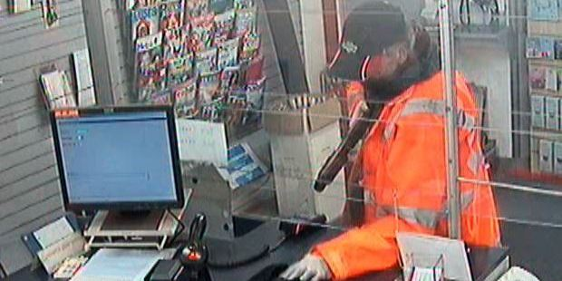 An armed robber wearing a hi-vis jacket has made off with cash from an Auckland branch of Kiwi Bank. Photo / NZ Police