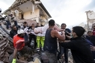 A rescued woman is carried away on a stretcher following an earthquake in Amatrice Italy, Wednesday, Aug. 24, 2016.