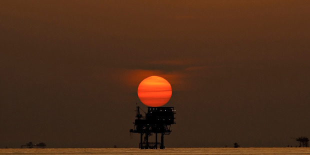 An offshore oil platform and wells are silhouetted by the setting sun in the Gulf of Mexico off the Louisiana coast. Photo / Derick E. Hingle