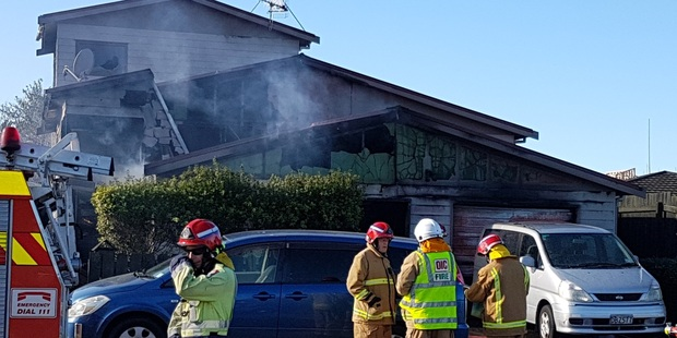 Firefighters at the scene of a house fire in Papamoa. Photo/Anna Whyte