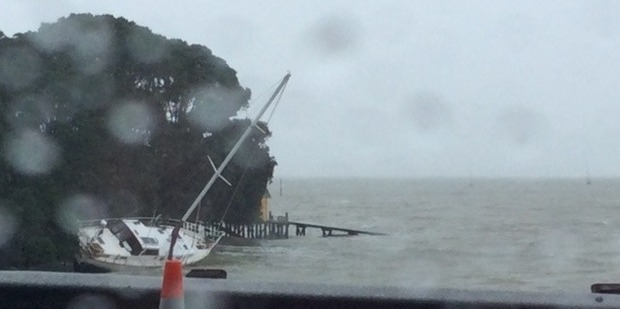 A yacht is washed up in a bay in Herne Bay Auckland as strong winds swept through the region last night. Photo / Gill Kimrich