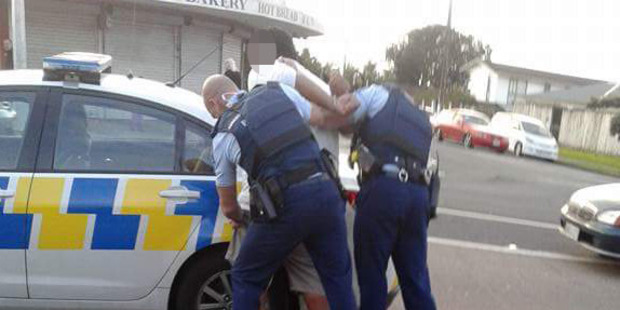 Police detain a suspect following a brawl at the Mangere branch at KFC yesterday. Photo / Facebook