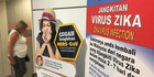 A traveller walks past an advisory on the Zika virus infection in Kuala Lumpur International Airport in Sepang, Malaysia. Photo / AP