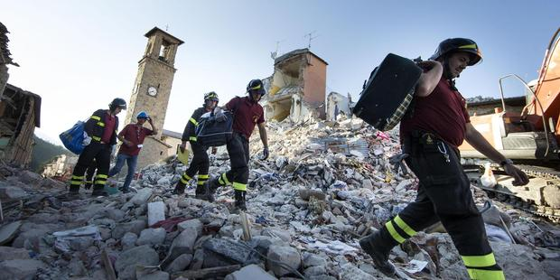 Firefighters carry personal belongings retrieved from houses, in Amatrice, central Italy. Photo / AP