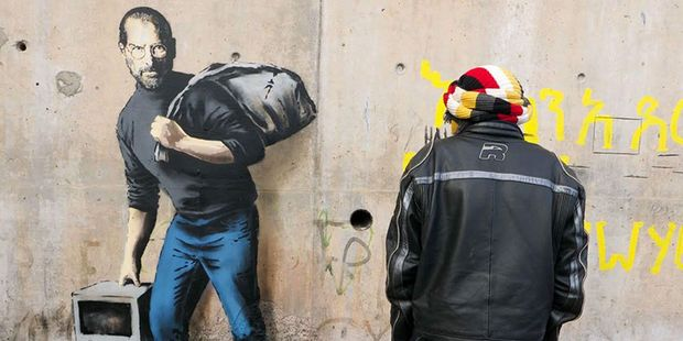 A man looks at a Banksy artwork in a refugee camp in Calais. The work shows the late Steve Jobs , founder of Apple, the son of a Syrian migrant.