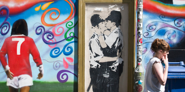 A famous 'Banksy' artwork is framed with a protective glass covering on the side of the Prince Albert pub in Brighton.