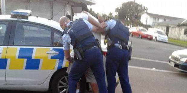 Police detain a suspect following a brawl at the Mangere branch at KFC. Photo / Facebook