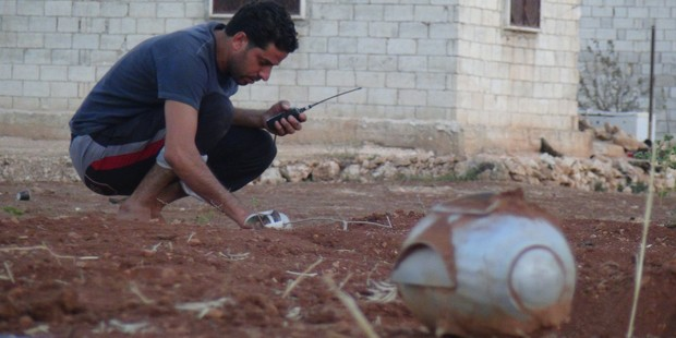 A man inspects pieces of cluster bomb after an airstrike on residential ares in Idlib, Syria last week. ASB Bank says its KiwiSaver funds will no longer invest in certain weapons makers. Photo / Getty