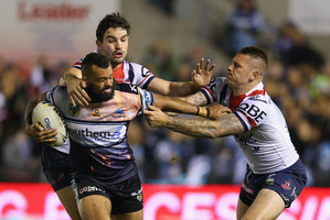 Jayson Bukuya of the Sharks is tackled by Roosters players at Shark Park in Sydney last night. Photo / Getty Images