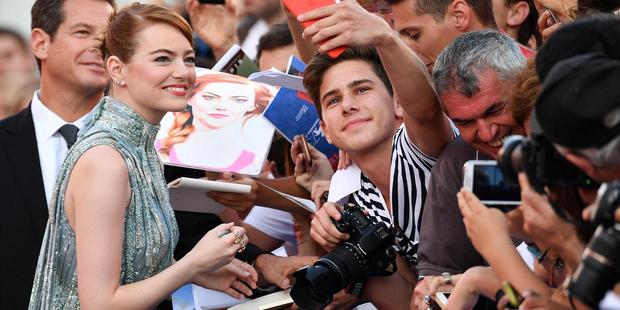 Actress Emma Stone sign autographs as they arrive on the red carpet for the film 'La La Land' that opens the 73rd Venice Film Festival in Venice, Italy. Photo / AP