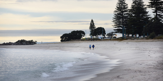 Early morning walkers still hit the beach after tsunami warning was issued yesterday morning. Photo/George Novak