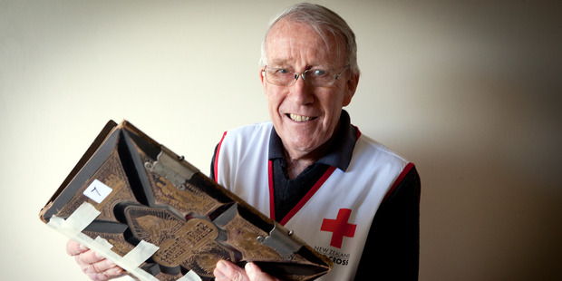 Red Cross volunteer David Garland with a bible from the 1800's at the Red Cross Book Fair. Photo/Andrew Warner