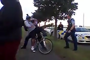 Still from Facebook video showing police pushing a young man from his bicycle in South Auckland. Photo / Supplied