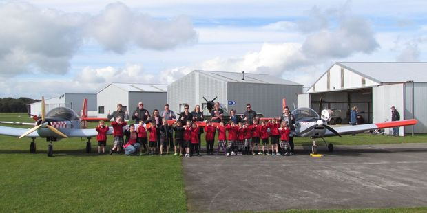 A class photo in front of the club trainer planes.