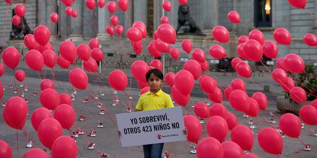 "Zaid, an 8-year-old Syrian refugee now living in Spain, poses with a sign reading in Spanish: ""I survived, 423 other children did not"", in front of the Spanish Parliament in Madrid. Picture / AP"