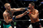 Conor McGregor punches Nate Diaz during their bout at UFC 202. Photo / AP
