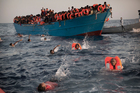 Migrants, most of them from Eritrea, jump into the water from a crowded wooden boat as they are helped by members of an NGO during a rescue operation at the Mediterranean sea. Photo / AP