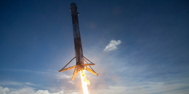 A SpaceX Falcon rocket booster lands on a platform in the Atlantic Ocean after launching a satellite into orbit earlier this year.